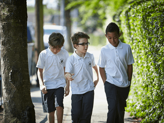 Three boys walking to school