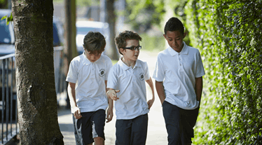 Three boys walking to school together
