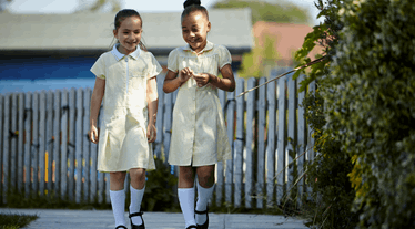Two girls in yellow dresses walking to school