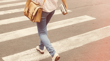 Young woman walking over zebra crossing