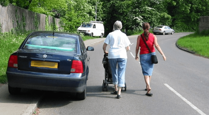 Women with pram walking in the road to get around a car on the pavement