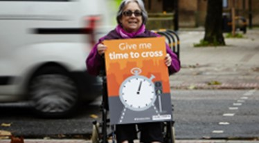 Women in wheelchair with 'give me time to cross' placard