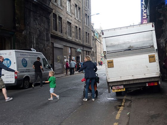 Child crossing the street because pagements are blocked by vans