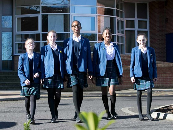 Five secondary school pupils standing in front of their school