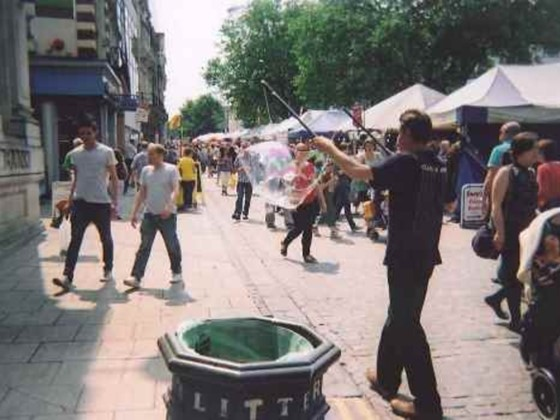 Photo of a community event in Norwich, street performers and market stalls