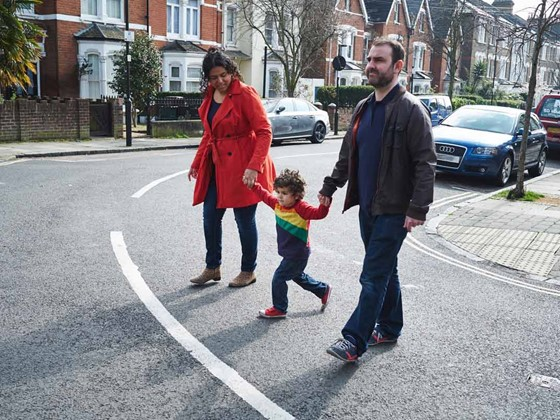 A mother and father crossing a road with a small child